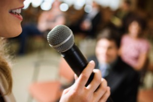 Woman delivering presentation at microphone