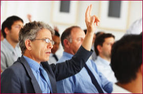 Man raises hand during a presentation