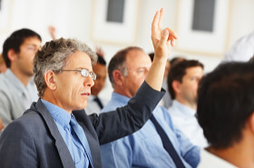 Audience member raises hand at a presentation
